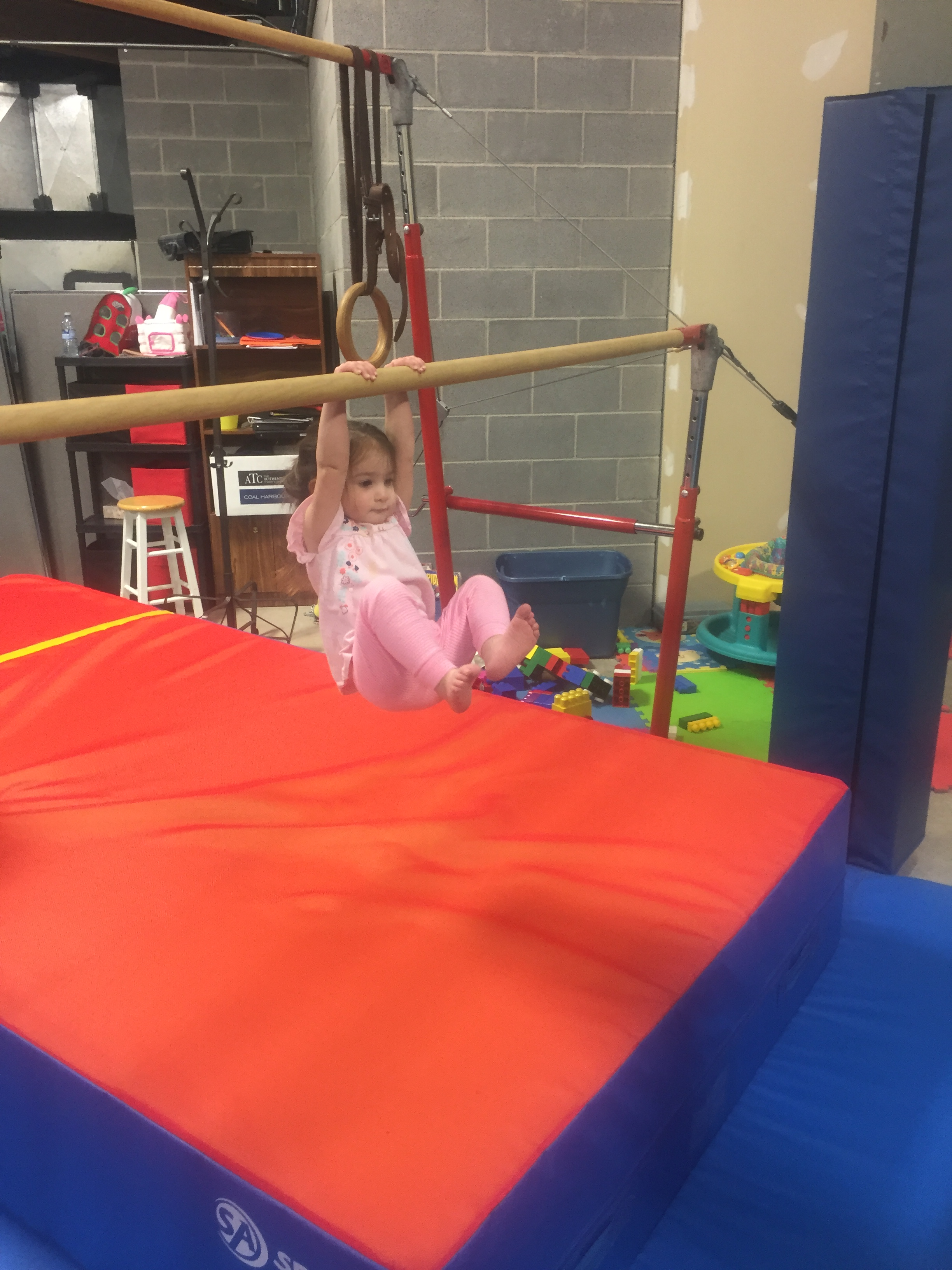 Naomi on the low bar at the gymnastics open gym.